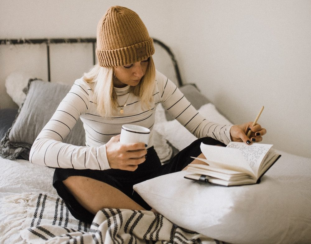 girl sitting down writing in her journal