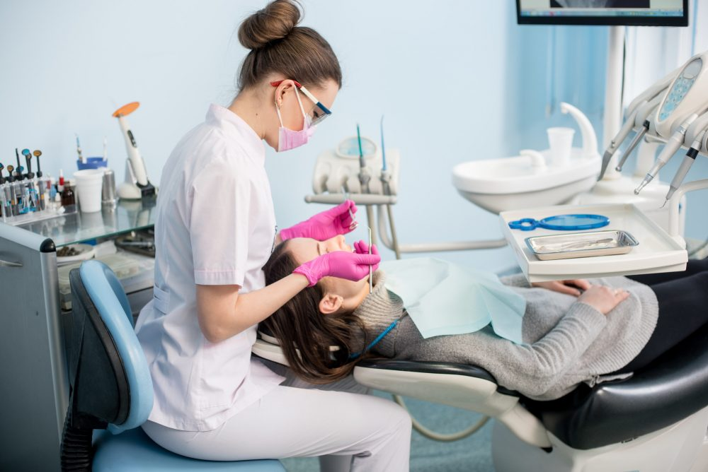 Female dentist with dental tools - mirror and probe checking up patient teeth at dental clinic office. Medicine, dentistry and health care concept. Dental equipment