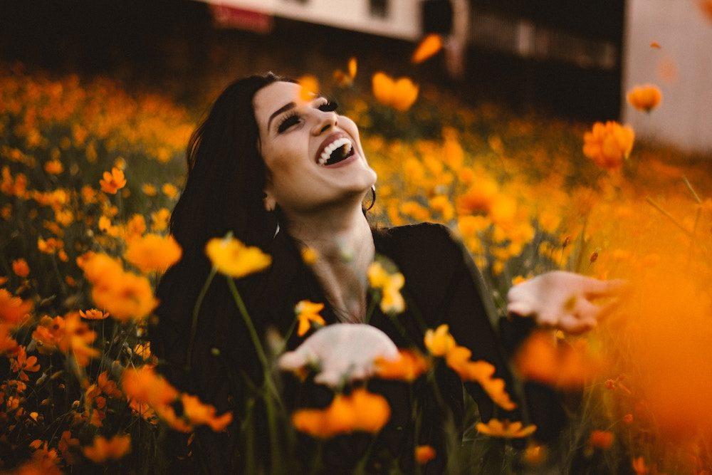 smiling woman in field of flowers