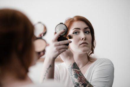 Woman applying blusher, highlighter, make up
