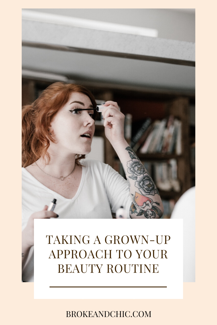 woman with red hair putting on mascara
