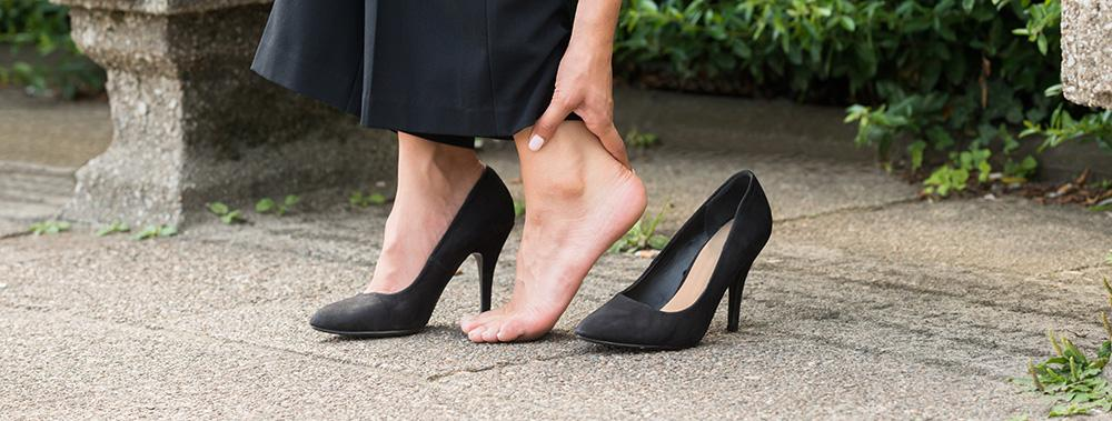 woman with heels off due to foot pain