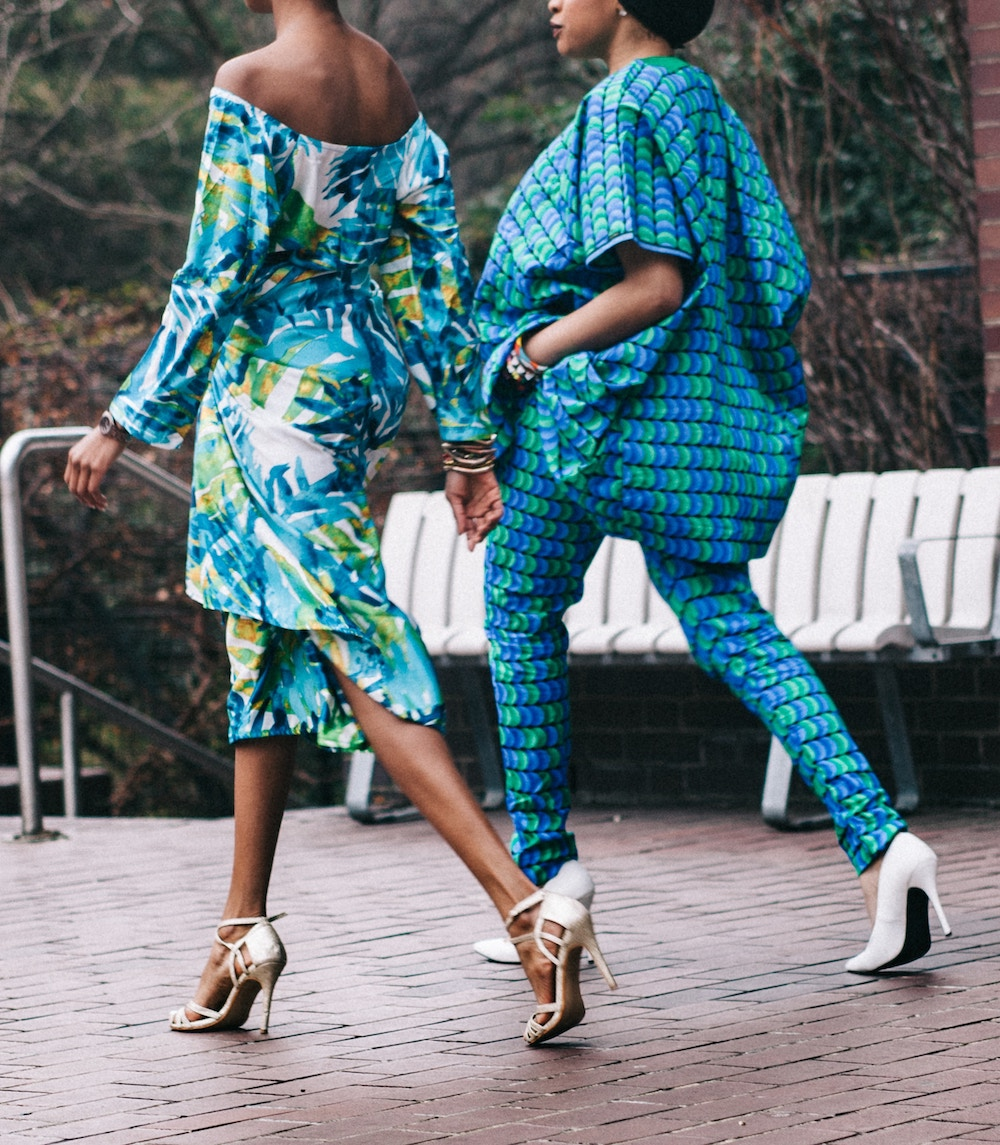 two women wearing statement outfits and high heels.