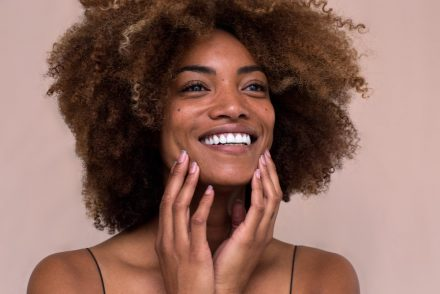 woman touching her face and smiling