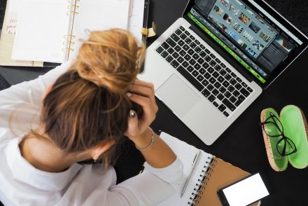 woman holding her head at computer