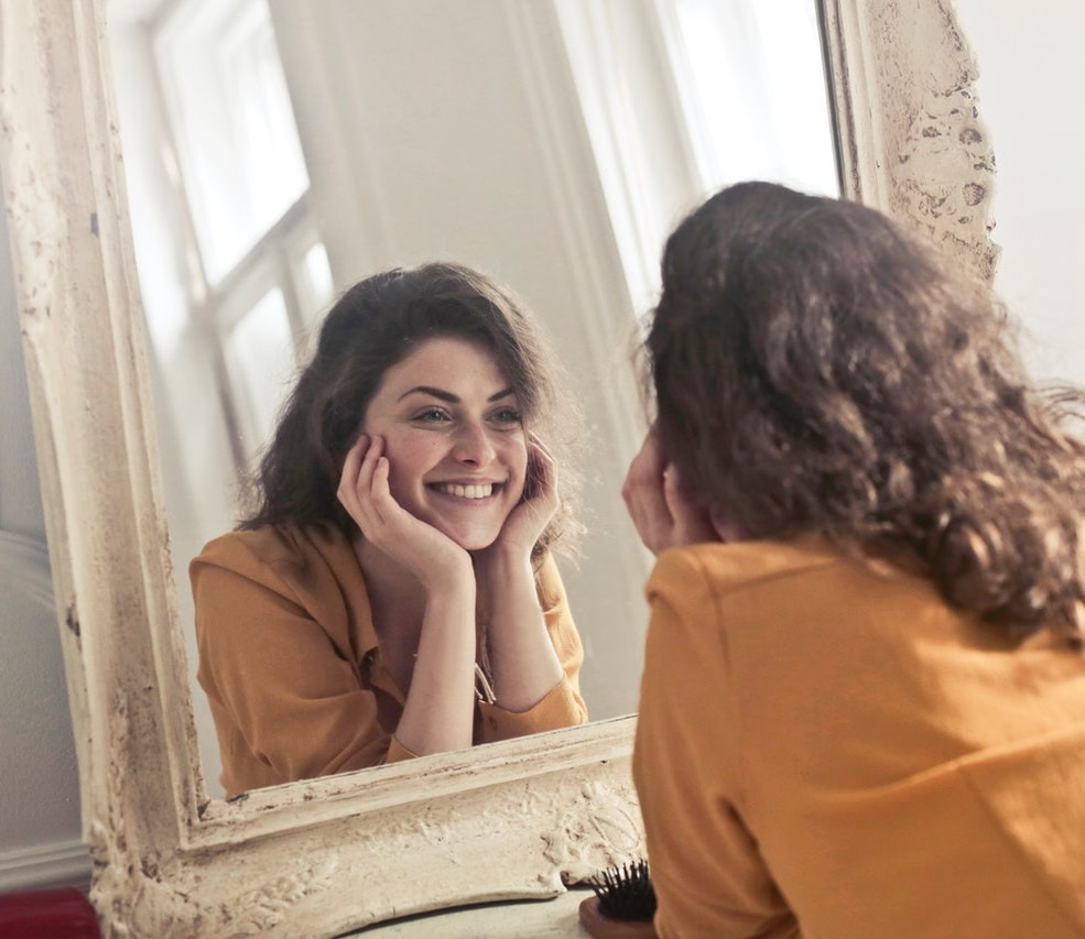 woman looking at herself in an antique mirror