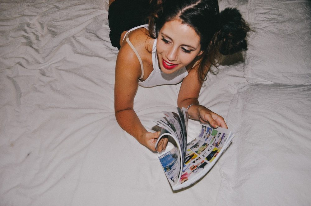 woman reading magazine on bed
