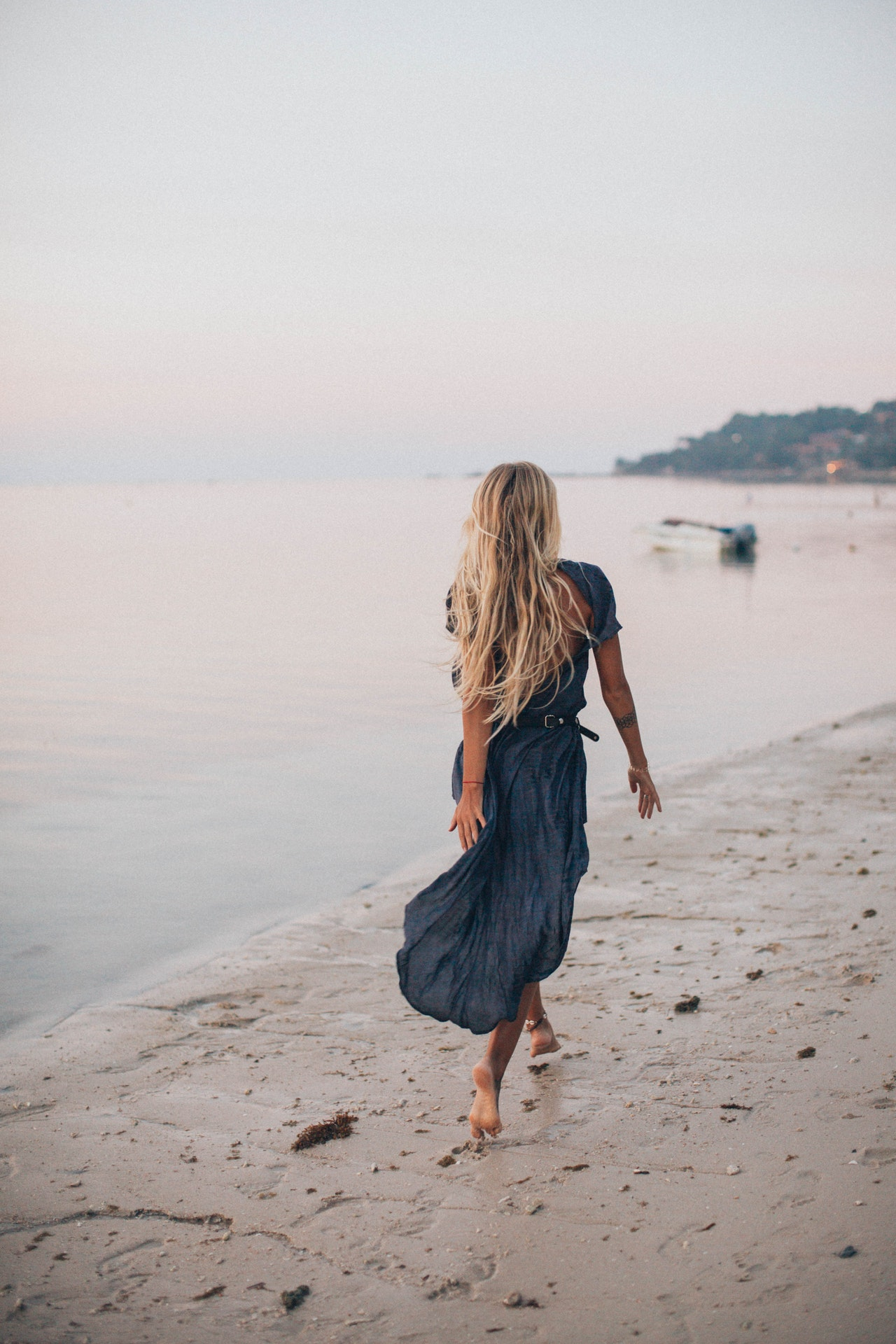 Woman in maxi dress walking along the sea shore.