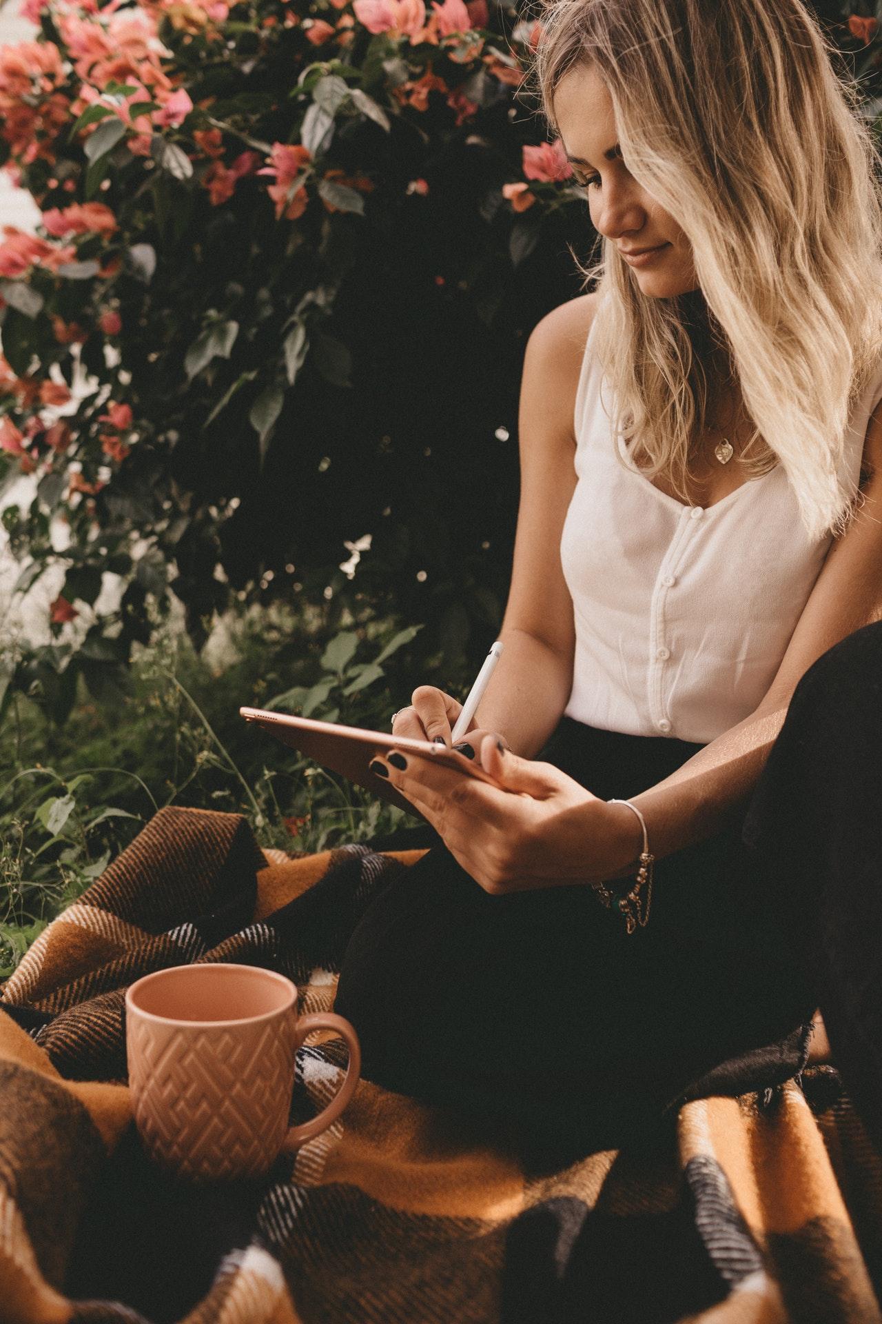 woman writing on iPad