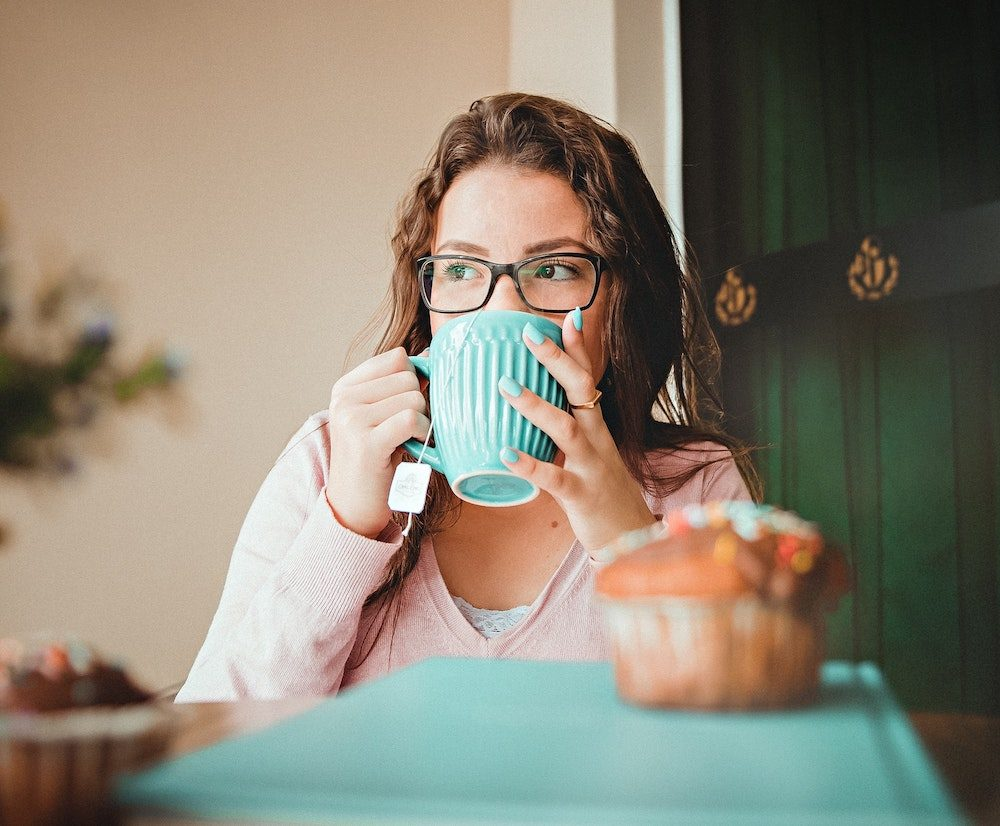 Woman drinking out of a teal mug