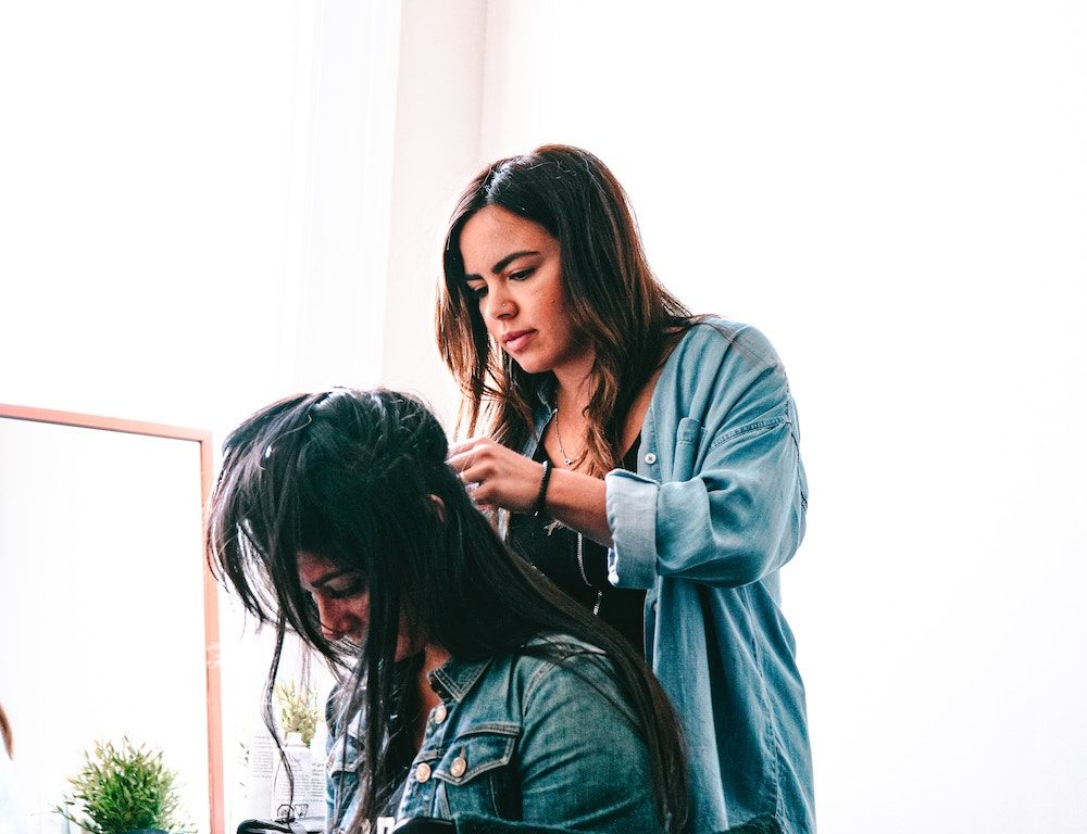 Stylist applying hair extensions