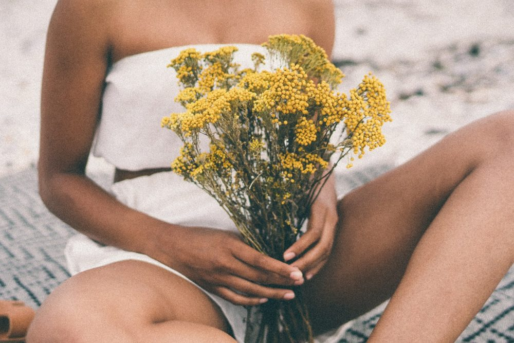 woman in white shorts holding yellow flowers