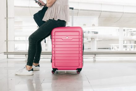 woman sitting on pink luggage bag