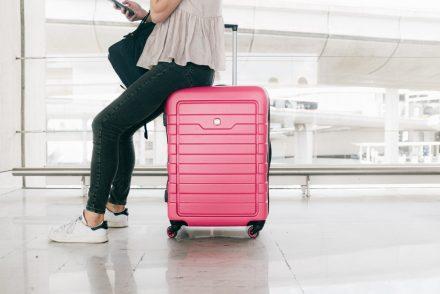 woman sitting on pink luggage bag