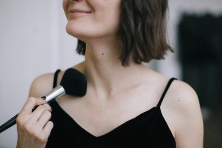 Woman using powder on her neck