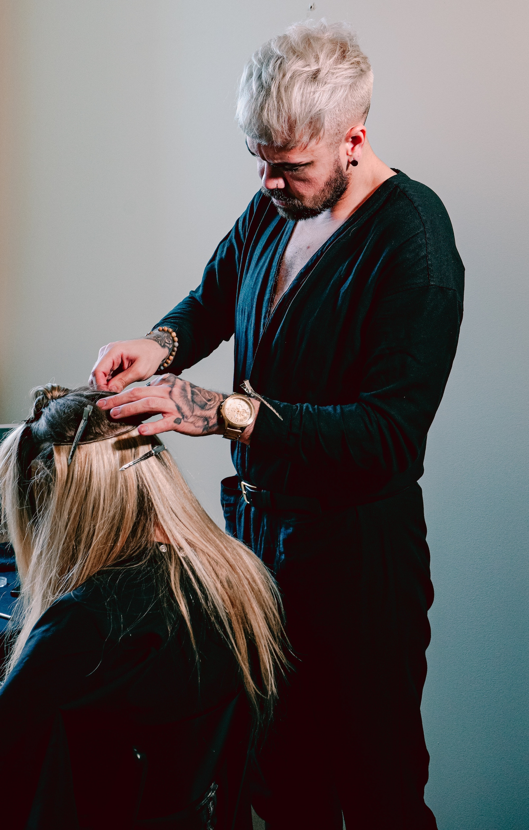 Hair stylist putting in clip-in extensions