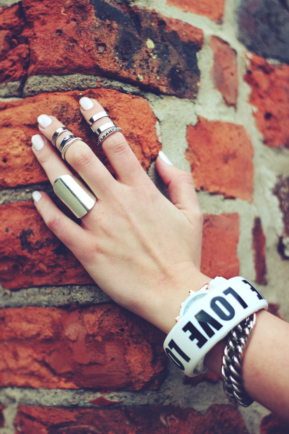 woman with white nails with silver jewelry.
