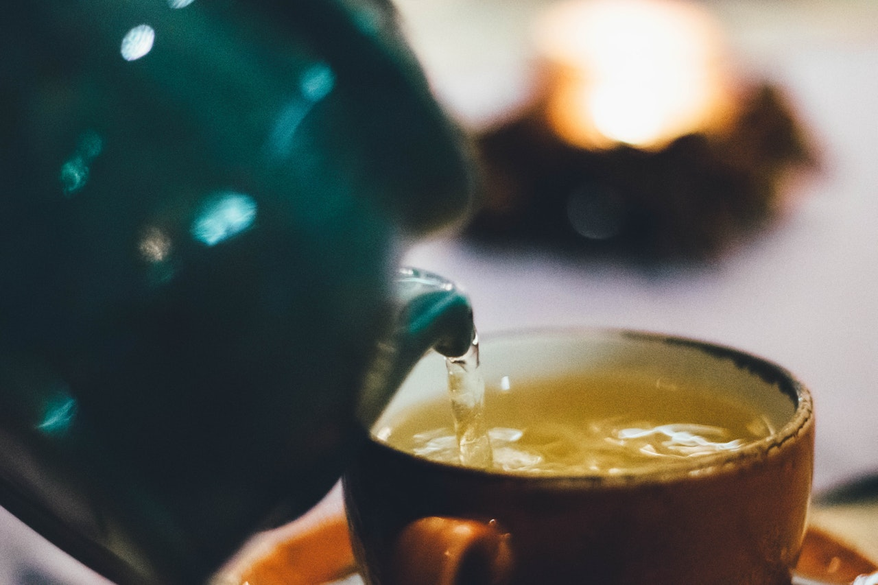 pouring green tea into a ceramic mug