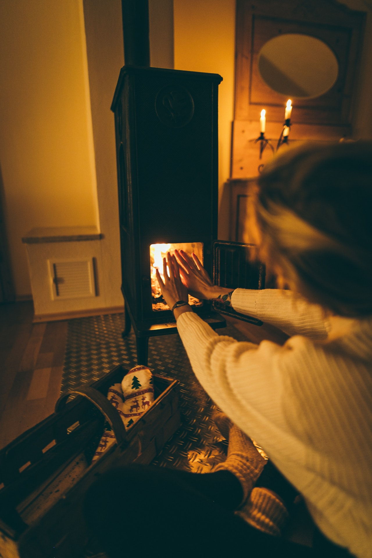 Woman warming hands in front of fire place