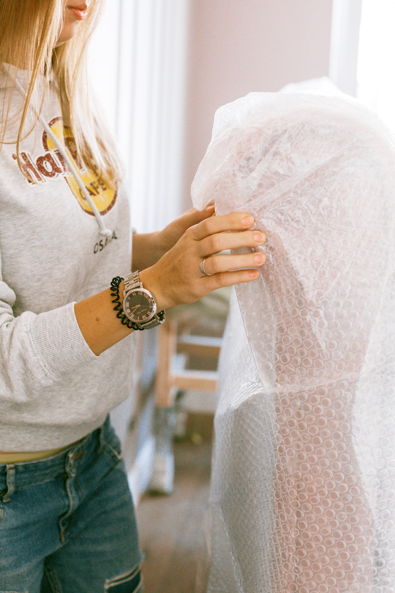 Woman wrapping furniture in bubble wrap