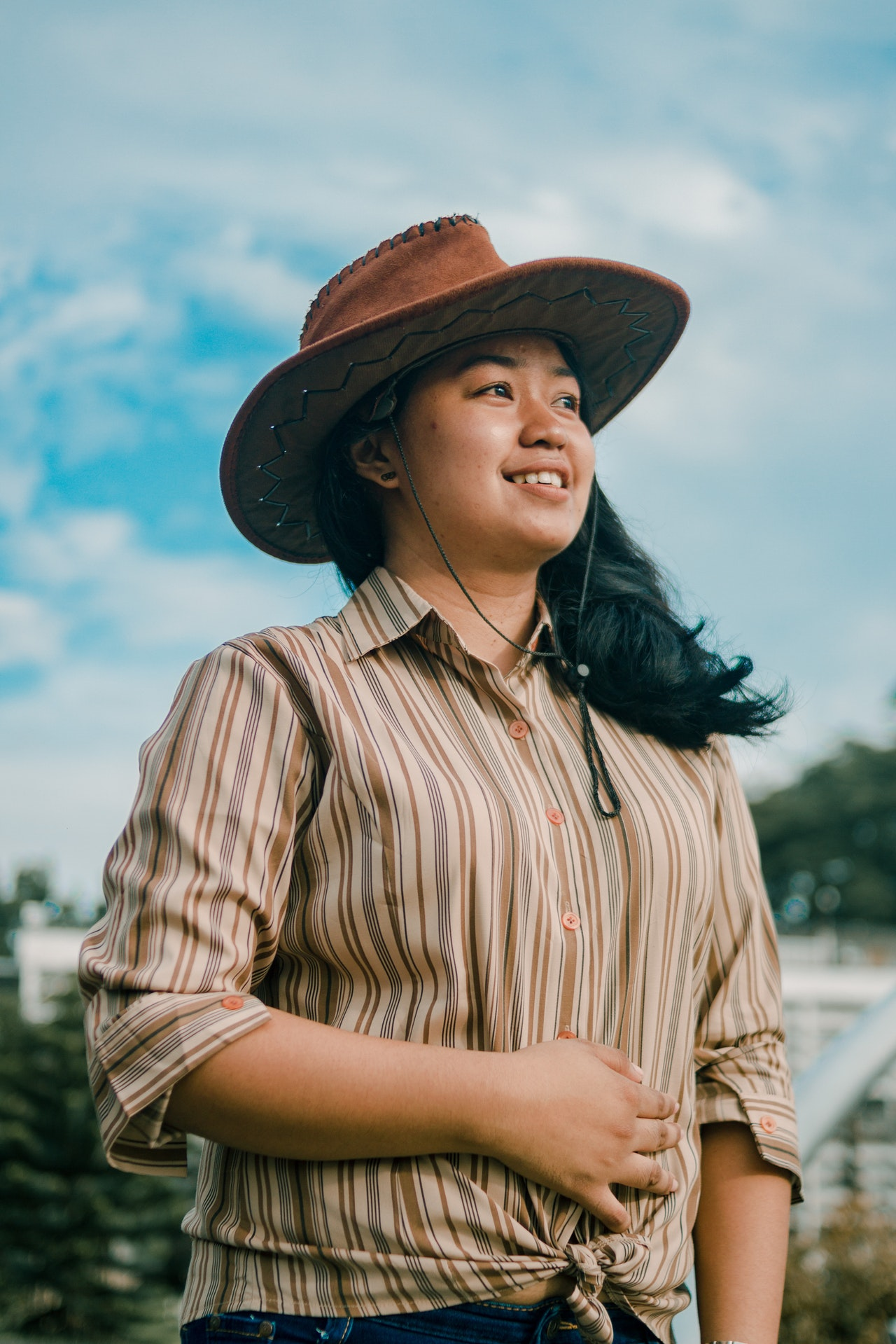 Woman wearing cowboy hat and button down shirt