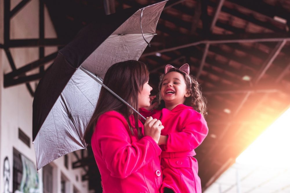 Mom and daughter under an umbrella