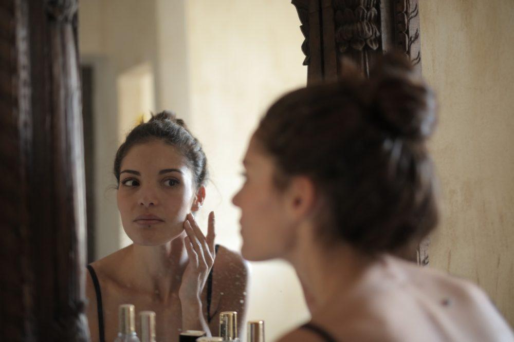 woman looking in mirror,