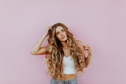 woman with long hair pink background