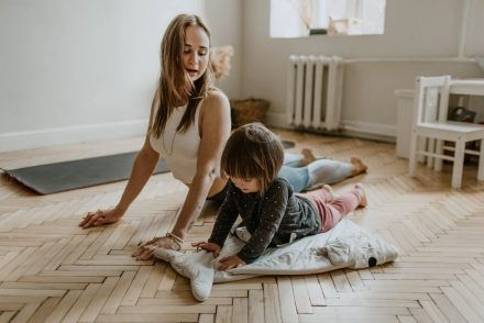 woman doing yoga with daughter