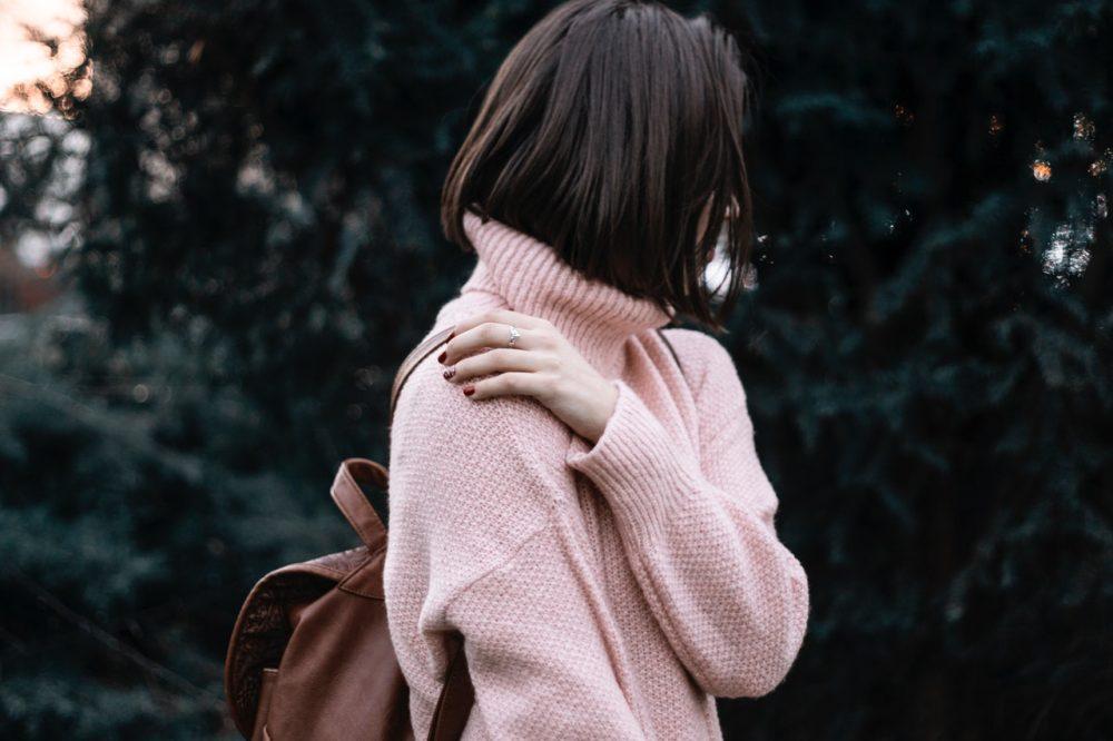 Woman touching her shoulder