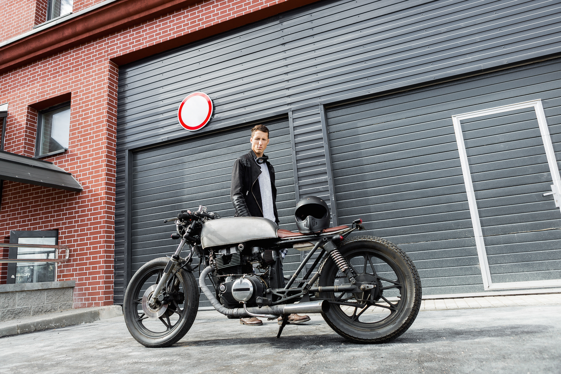 Handsome rider man in black leather biker jacket look to his classic style cafe racer motorcycle industrial gates as background. Bike custom made in vintage garage. Brutal fun urban lifestyle.