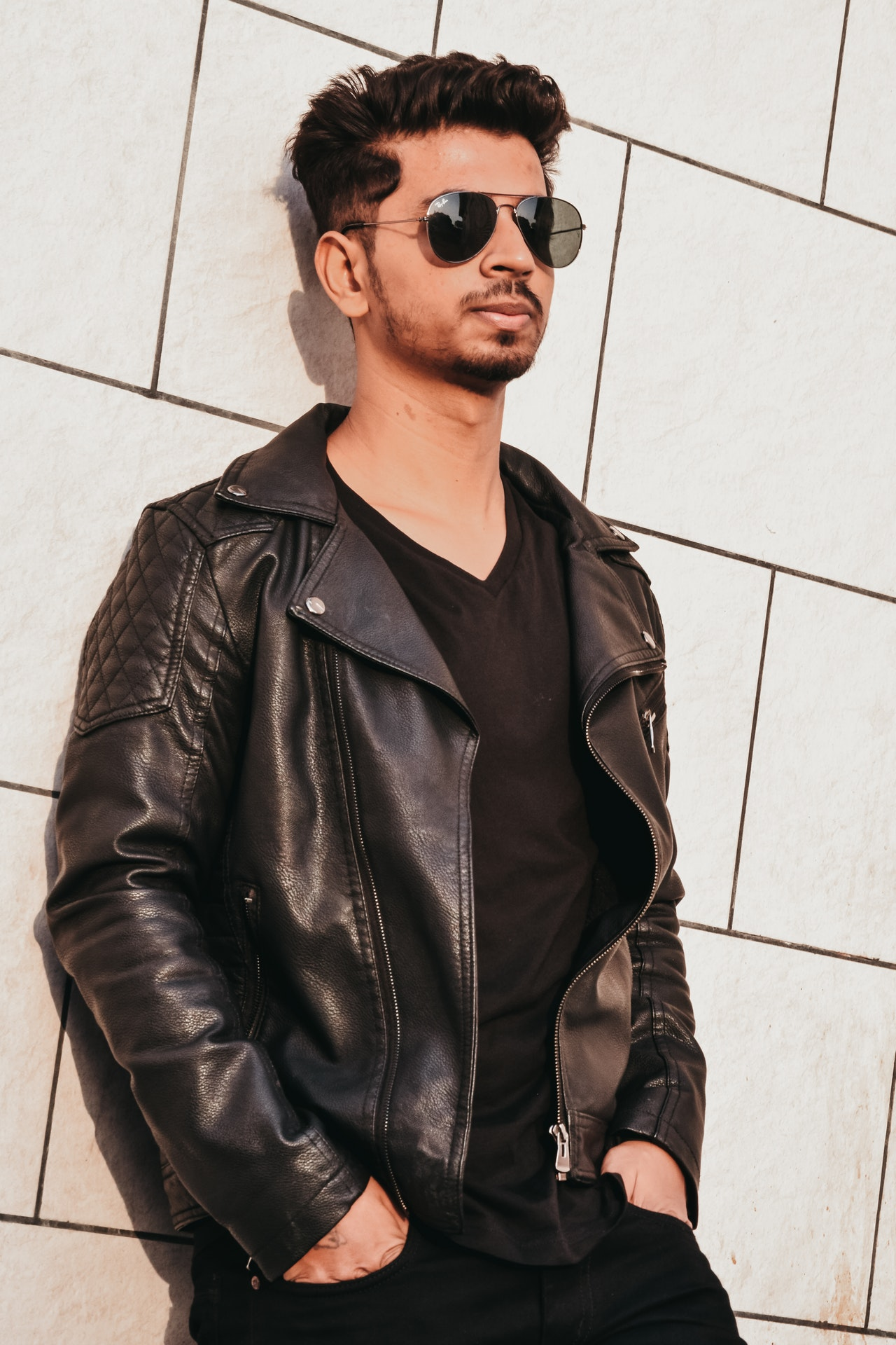 man wearing a black leather jacket leaning against a white wall.