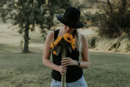 Woman smelling sunflowers