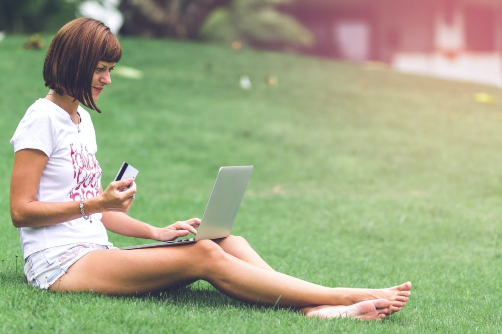woman sitting on lawn with credit card