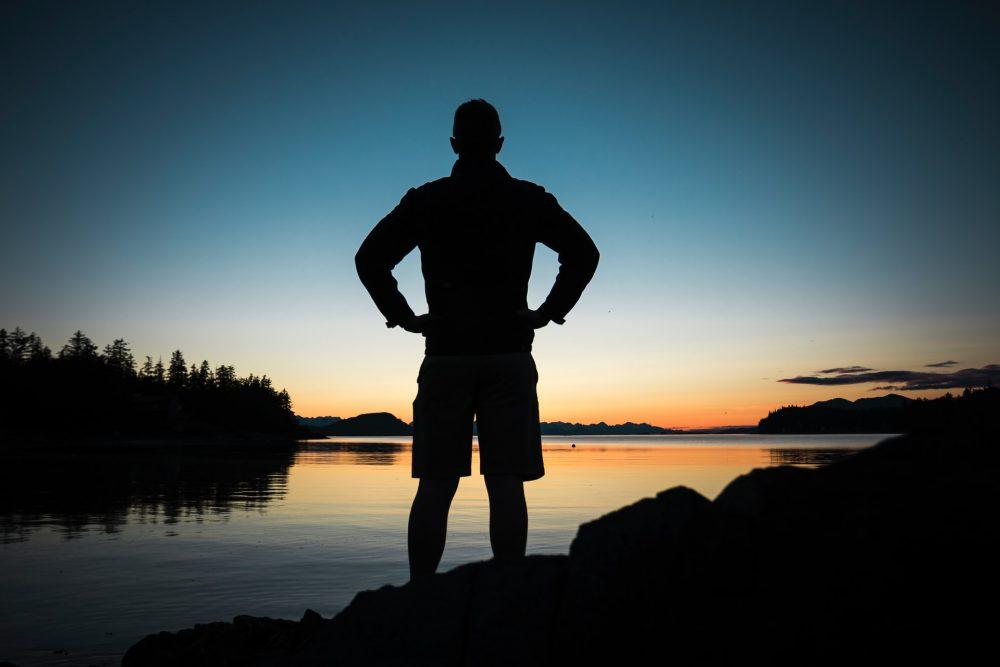 man's silhouette by lake