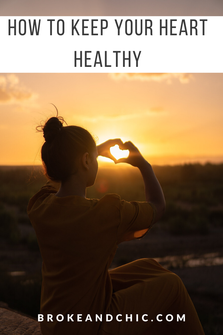 woman making heart symbol with hands at sunset.