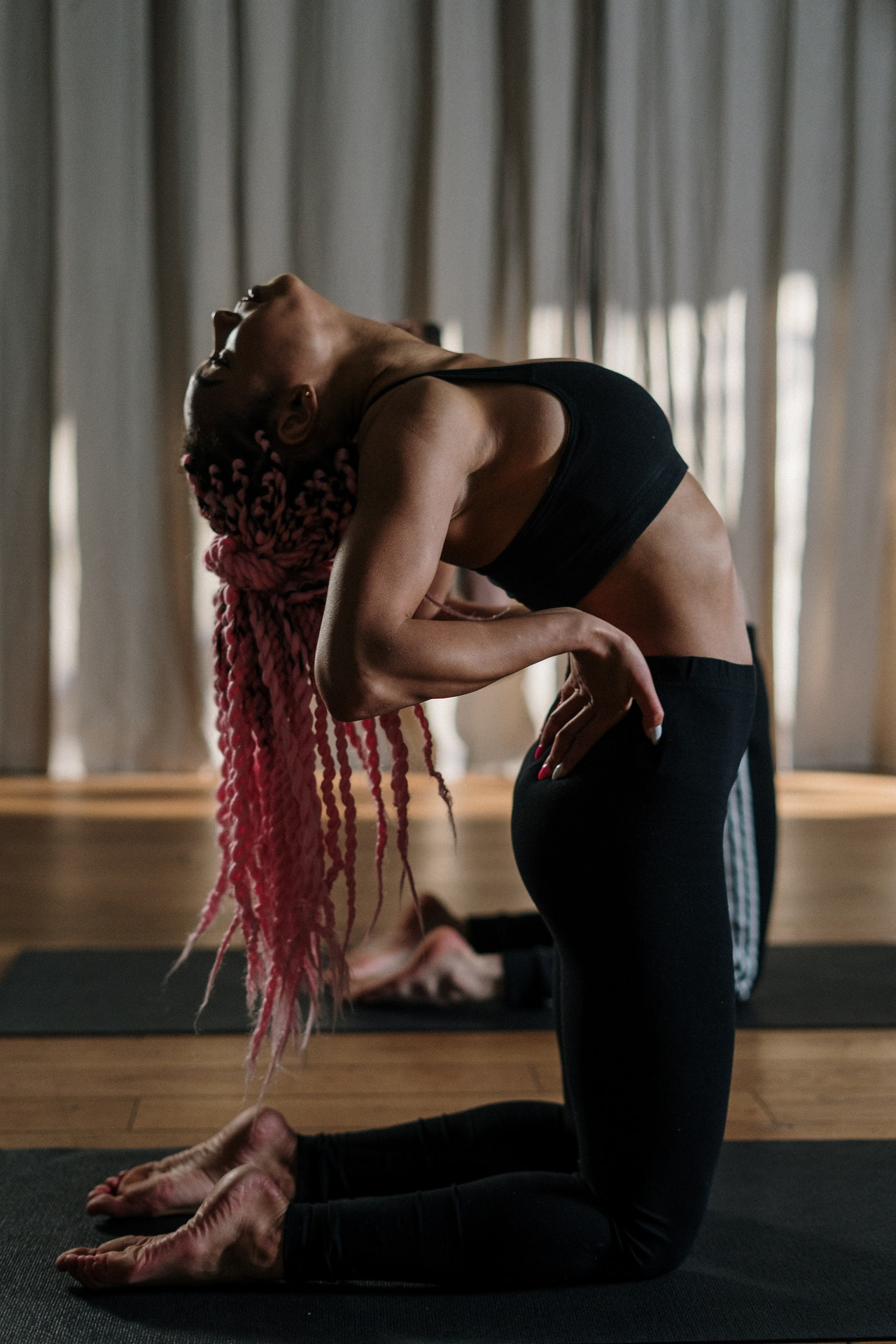 woman with pink braids doing a camel pose