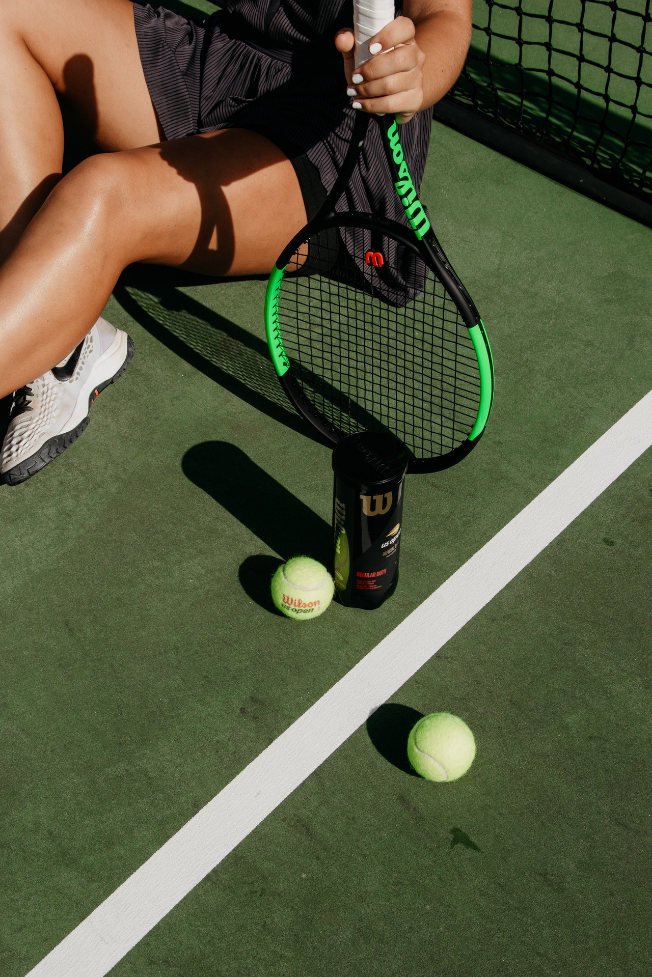 Woman with white nail polish holding a tennis racket