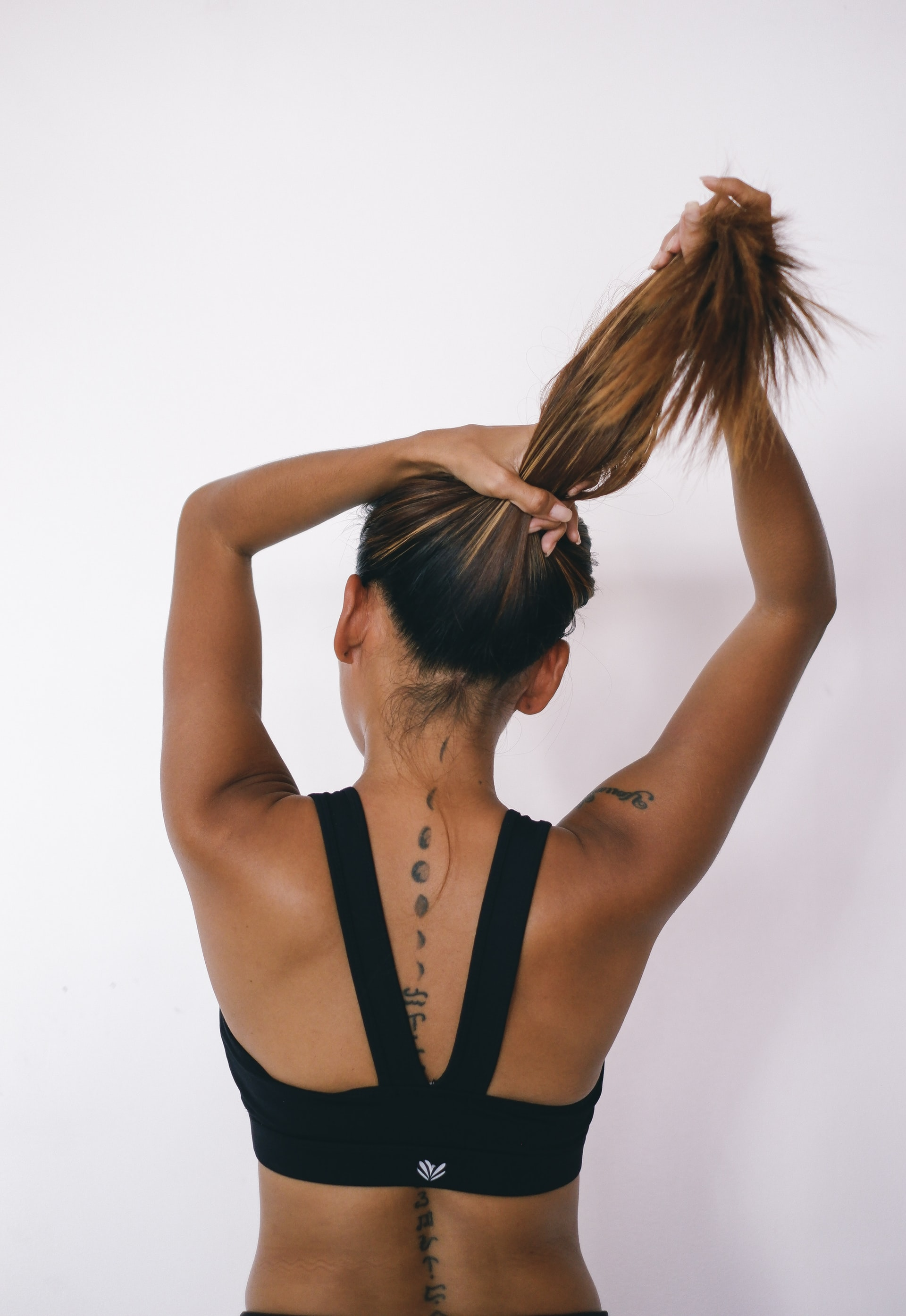 Woman in sports bra putting hair in ponytail