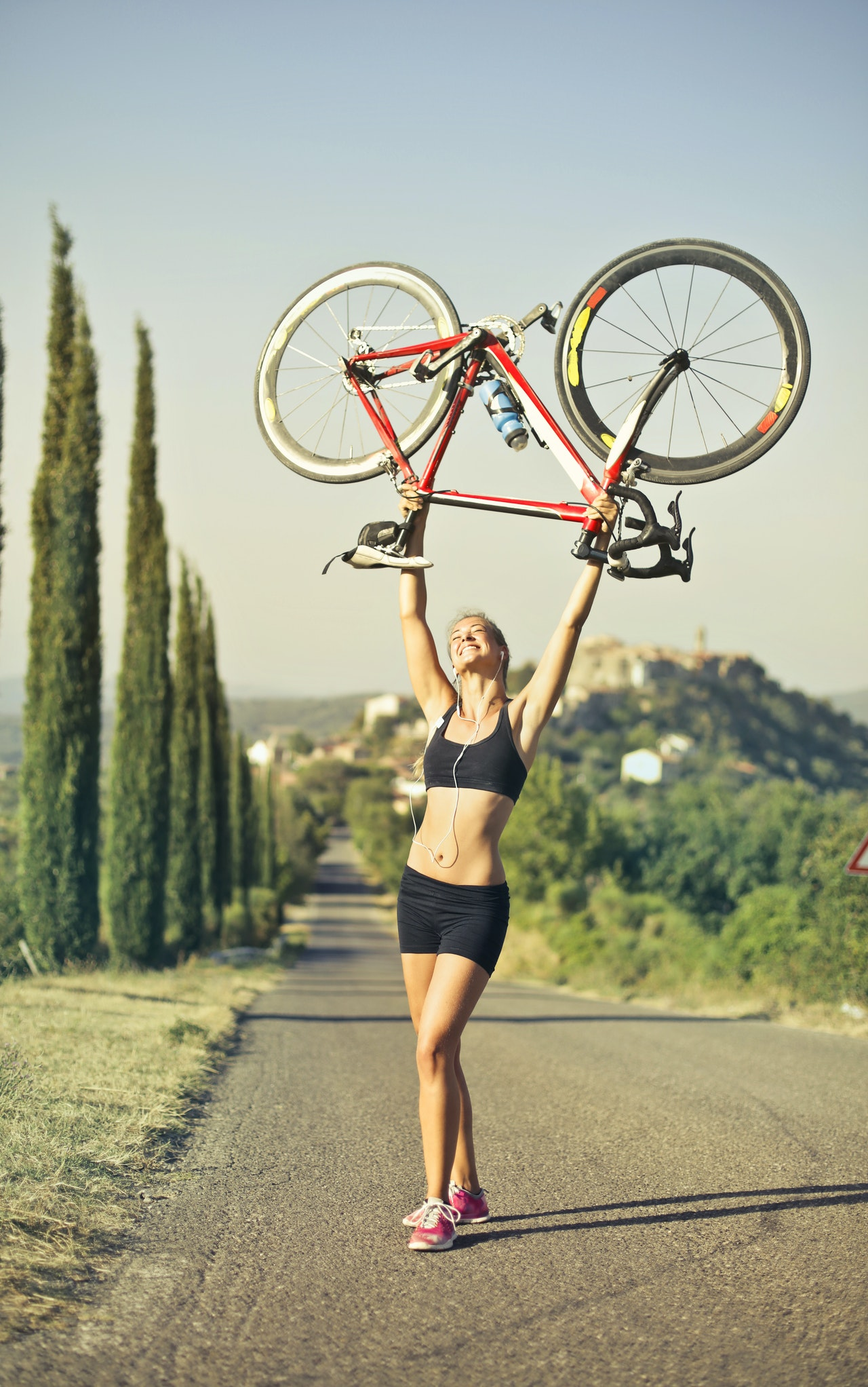 woman holding a bike in the air