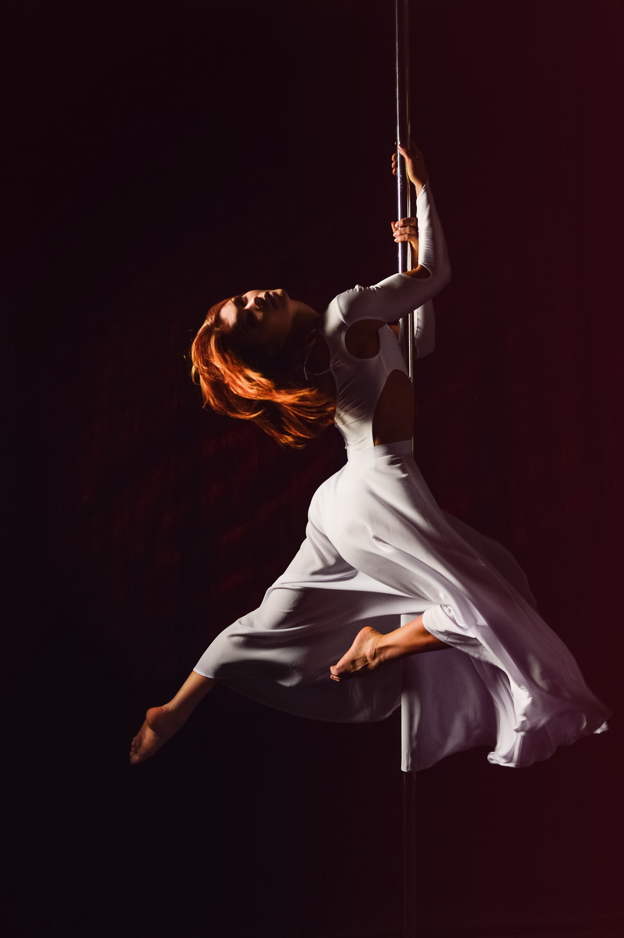 Woman in white dress pole dancing