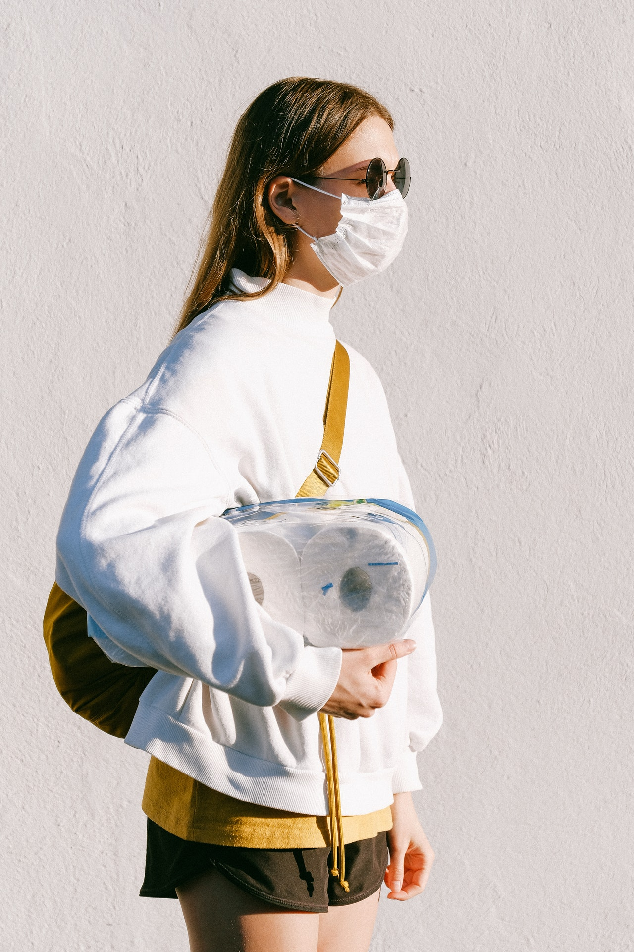 woman holding toilet paper and wearing face mask for coronavirus