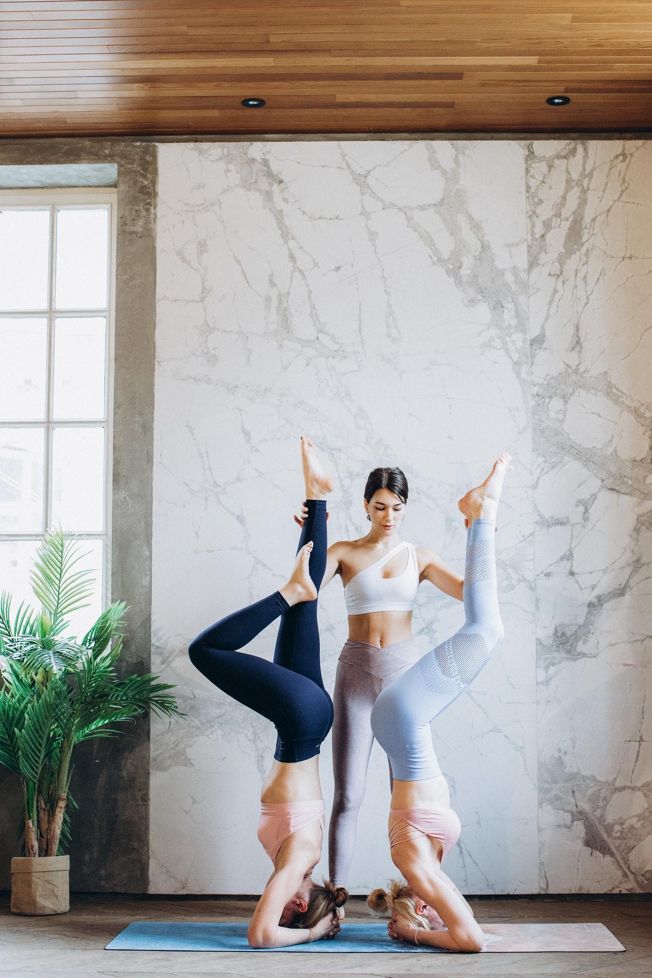 women doing acro yoga