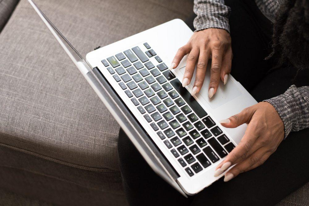 woman's hands using laptop