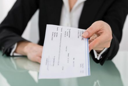 Woman holding paycheck