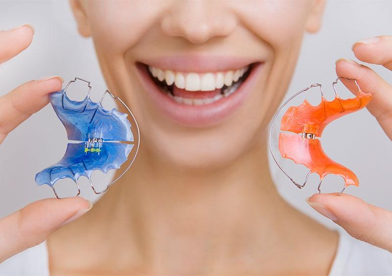 woman holding up two retainers