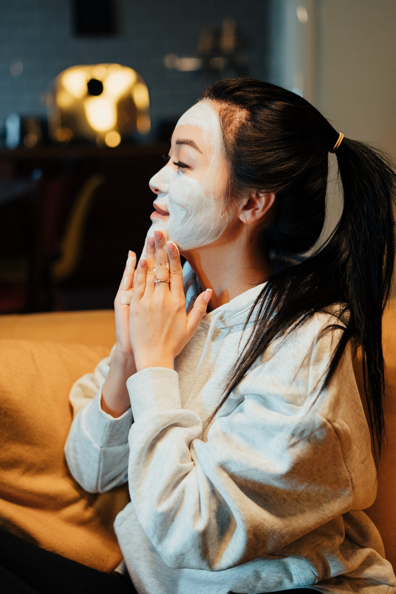 woman putting on a clay face mask
