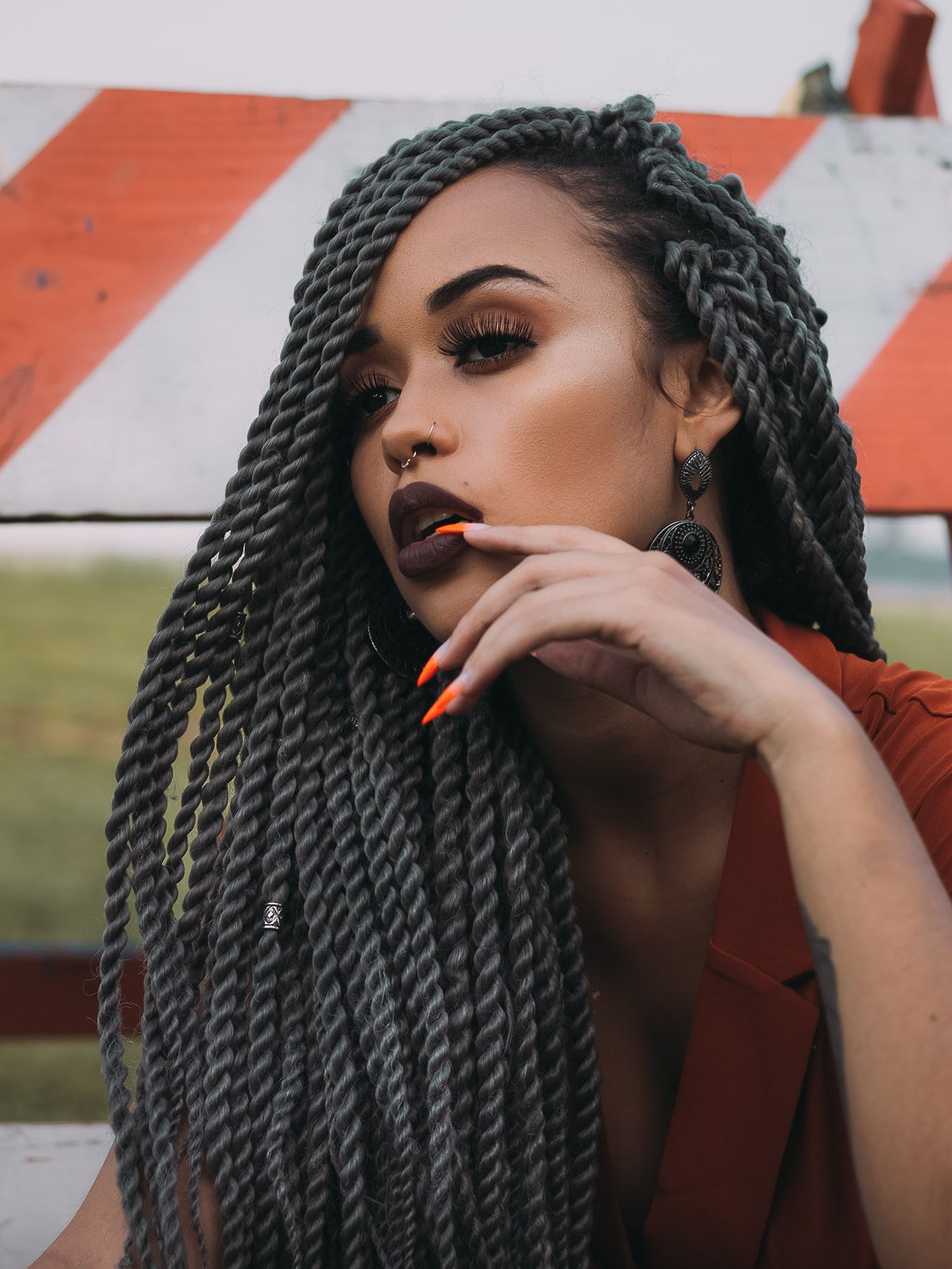 woman with orange nails and grey braids