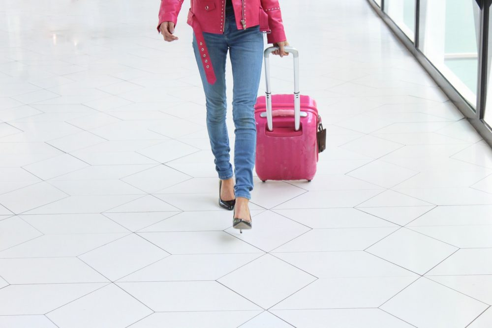 woman pulling pink luggage bag