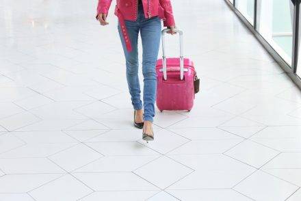 woman pulling pink luggage bag